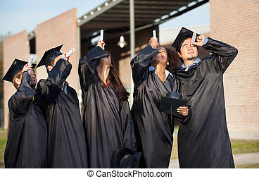 Multiethnic university students in graduation gown looking through certificates on campus
