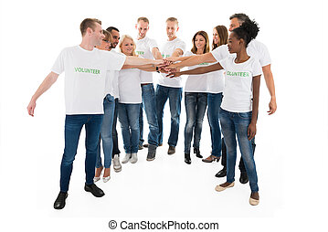 Multiethnic Volunteers Stacking Hands Against White Background