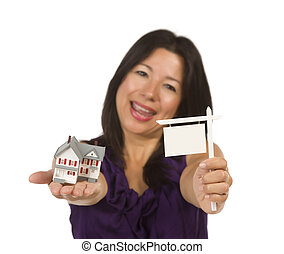 Multiethnic Woman Holding Small Blank Real Estate Sign and House in Hand Isolated on White Background - Ready for Your Own Message.