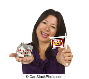 Multiethnic Woman Holding Small Sold For Sale Real Estate Sign and House in Hand Isolated on White Background.