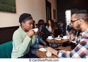 Multiethnic young couple talking over drinks in a cafe