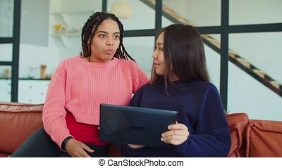 Multiethnic young women sharing tablet pc on sofa