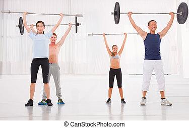 multiethnische gruppe, von, leute, trainieren, mit, weightlifting, bar, in