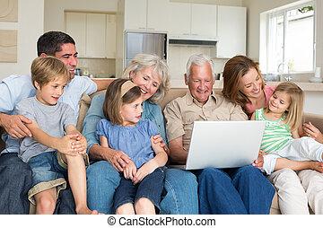 Multigeneration family using laptop in living room - Smiling...