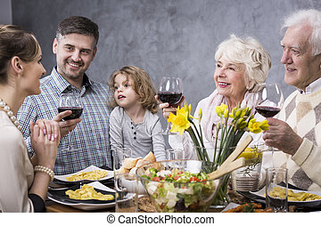 Multigenerational family at a dinner table drinking a toast...