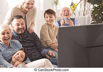 Multigenerational family watching television