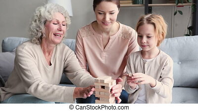 Multigenerational female family playing jenga board game together. Happy 3 three generations of women - old senior granny, young mother and small child granddaughter enjoying leisure activity at home.