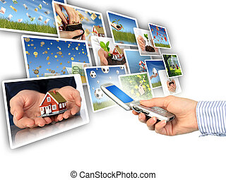 Multimedia concept. - Mobile phone in hand. Isolated over...