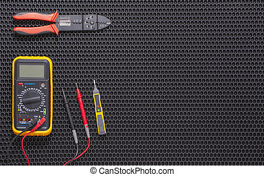 Multimeter, indicator screwdriver and wire stripper on a black rubber mat.