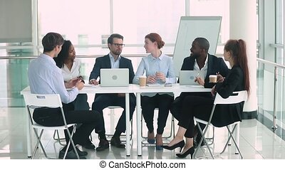 Multinational businesspeople sitting at table negotiating...