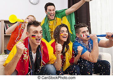 Multinational football supporters celebrating a goal