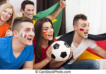 Multinational friends cheering football match at home