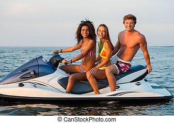 Multinational friends sitting on a jet ski