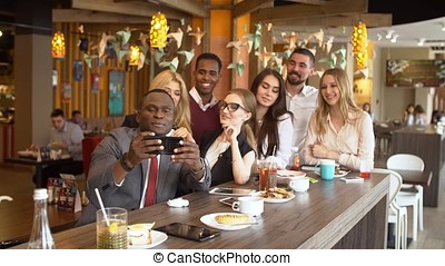 Multinational group of friends in a cafe doing selfi