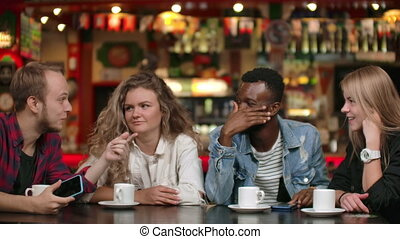 Multinational group of man and woman sitting together at a...