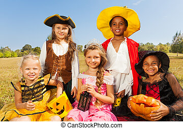 Multinational kids in Halloween costumes sitting together on the grass with pumpkin and look happily