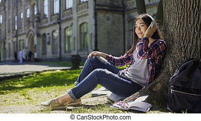 Multinational young woman in headphones sitting under tree, listening to music