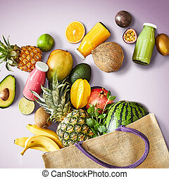 Multiple assorted fruits including pineapples star fruit avocado and oranges spilling out of canvas bag