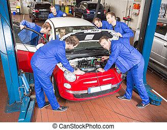 Multiple Auto mechanics repairing a car in garage