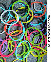 Multiple colored rubberbands in a pile on a gray textured background