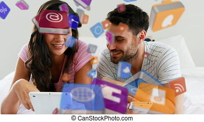 Animation of multiple digital icons falling over man and woman using digital tablet and smartphone at home. Global online network digital interface technology concept digitally generated image.