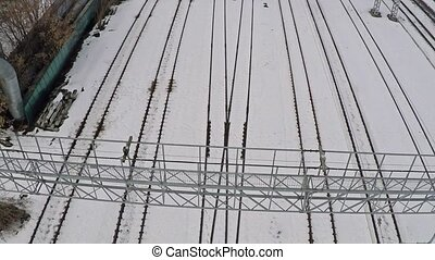 Multiple electrified railway tracks and switches in snow. Aerial view