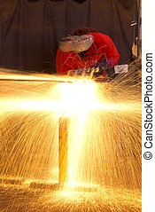 Multiple exposure of welder in workshop manufacturing metal construction by showering sparks from torch.