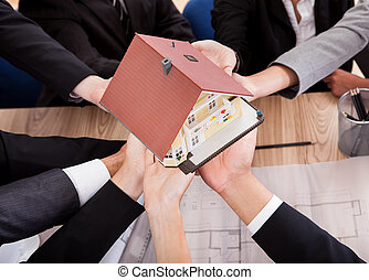 Multiple hands of diverse business people supporting a model house conceptual of partnership and teamwork