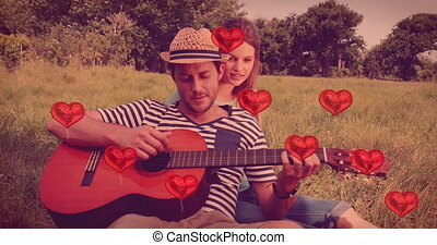Multiple heart balloons floating against man playing guitar for his woman in the woods