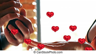 Animation of multiple red heart balloons floating over mid section of man putting ring on woman. Happy Valentines Day celebration concept digitally generated image.