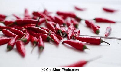 Multiple red chili peppers falling and bouncing at white ...