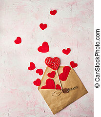 Multiple red hearts flying out of a brown paper envelope on pink colored background. Valentine's day concept.