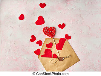 Multiple red hearts flying out of a brown paper envelope on pink colored background. Valentine's day concept. Top view