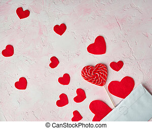 Multiple red hearts flying out of an envelope on pink colored background. Valentine's day concept. Top view