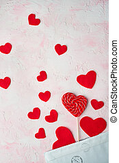 Multiple red hearts flying out of an envelope on pink colored background. Valentine's day concept.