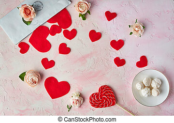 Multiple red hearts, sweets, flower heads, envelope on pink colored background. Valentine's concept.