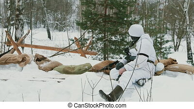 Multiple shots. Man Dressed As German Wehrmacht Infantry Soldiers In World War II Hidden Sitting With Weapon In An Ambush In Trench In Winter Day.