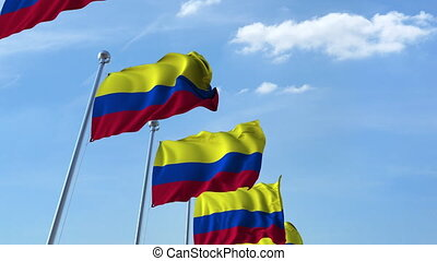 Multiple waving flags of Colombia against the blue sky