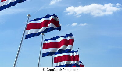 Multiple waving flags of Costa Rica against the blue sky -...