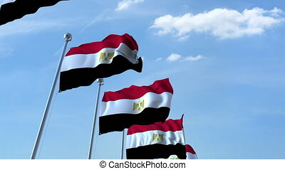 Multiple waving flags of Egypt against the blue sky