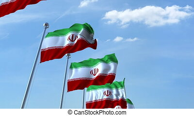 Multiple waving flags of Iran against the blue sky