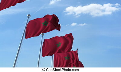 Multiple waving flags of Morocco against the blue sky