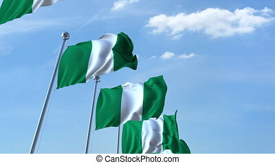 Multiple waving flags of Nigeria against the blue sky