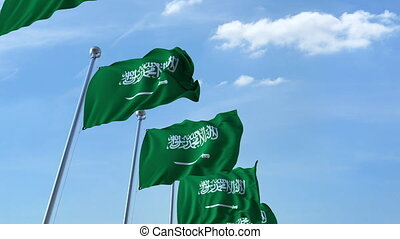 Multiple waving flags of Saudi Arabia against the blue sky -...