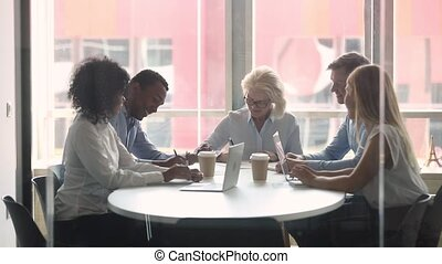 Multiracial business partners entities sitting in board room...