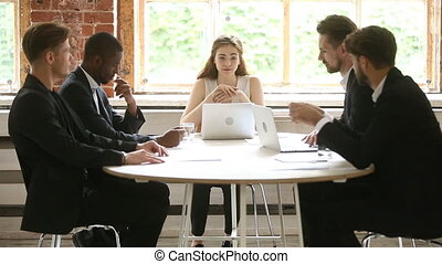 Multiracial businessmen listening to female company boss talking holding meeting