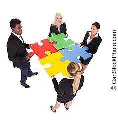 Multiracial Businesspeople Holding Jigsaw Puzzle