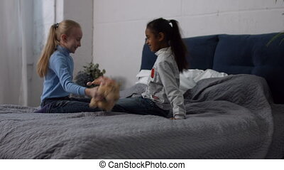 Multiracial children playing plush toys at home