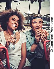 Multiracial couple having snack while riding on a sightseeing bus