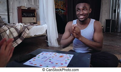 Multiracial couple playing board game. Mane throws dice and...